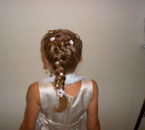 Mädchenfrisur mit Zopf und floralen Haarspangen