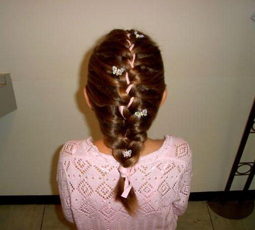 Mädchenfrisur mit eingeflochtenem Bändchen und Haarspangen